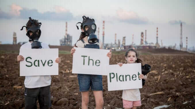 Save the planet. Young kids holding signs standing near a refinery with gas masks