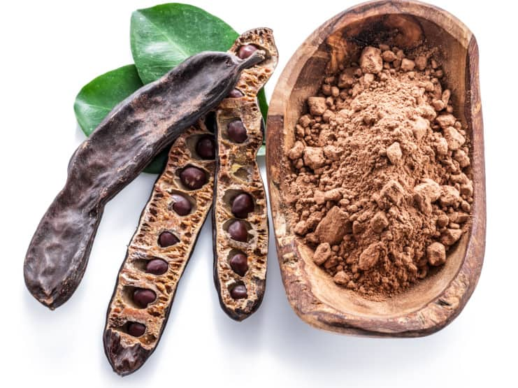 Carob pods and carob powder in the wooden bowl.