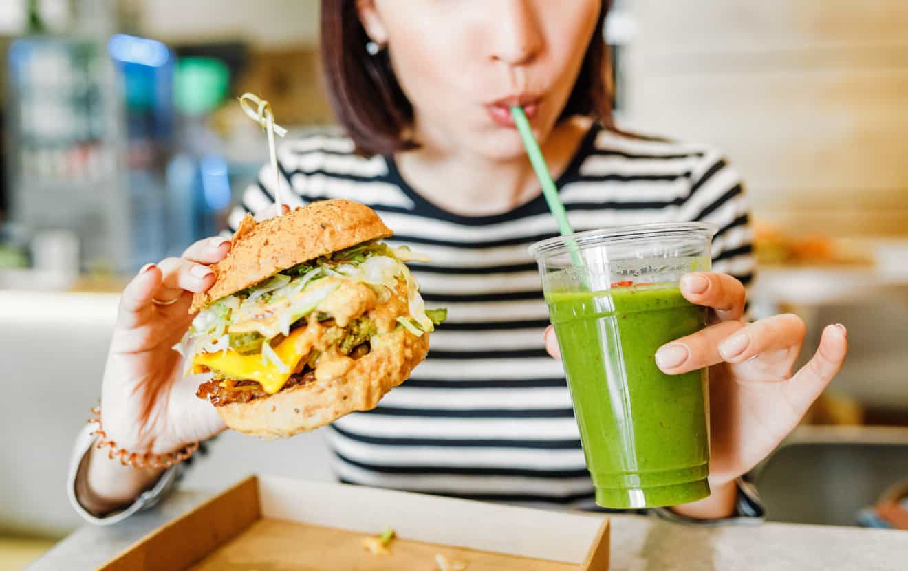 A young woman drinks green smoothies and eats a burger in a vegan fast food restaurant