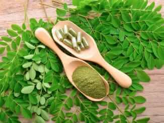 moringa leaf and powder capsule on wooden background