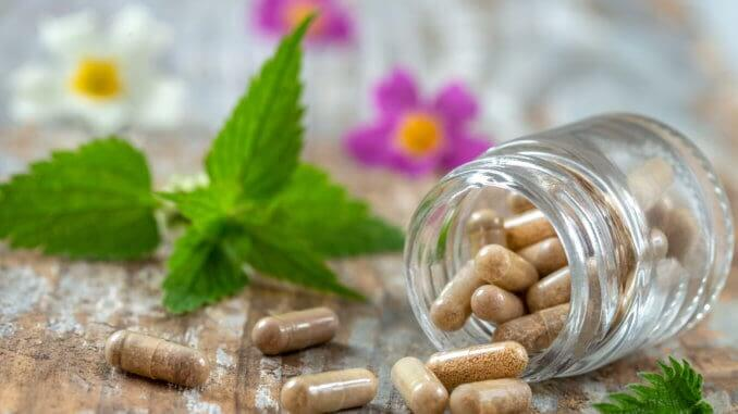 Bottle of pills food suplements healthy medicine medication health care treatment additives pharmacy with medicinal fresh plants and flowerson background