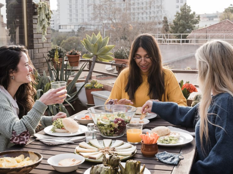 Happy multiracial friends eating breakfast