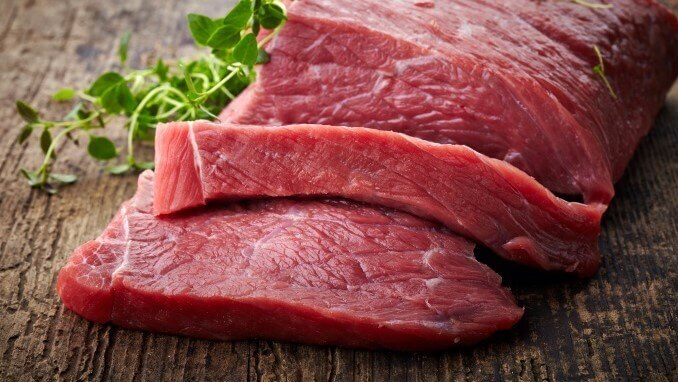 red raw meat on old wooden table