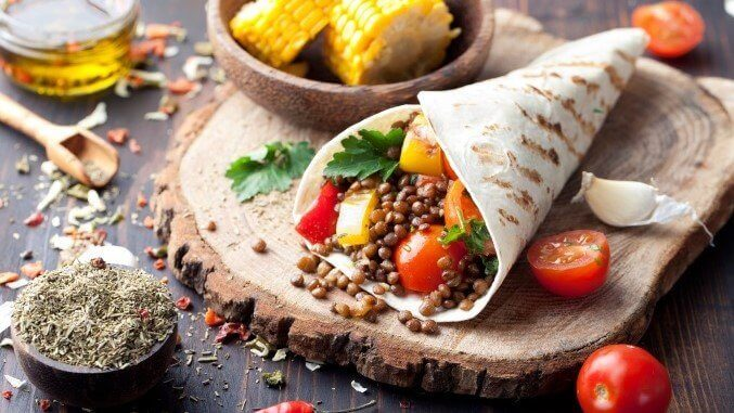 Vegan tortilla wrap, roll with grilled vegetabes, lentil, corn cob.