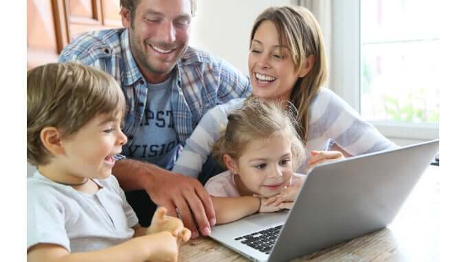 a family with two kids sits in front of a computer