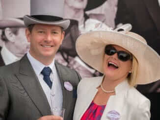 Couple at Royal Ascot laughing at camera
