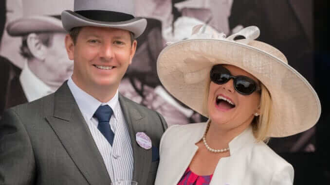 Couple at Royal Ascot laughing at camera