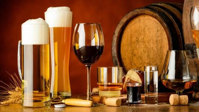 Bier- und Weingläser vor einem Barrique-Fass